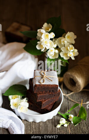Chocolate mascarpone brownies stacked with flowers on wooden table - Stock Photo