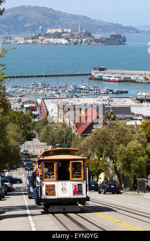 A Cable Car Going down Hyde Street in Downtown San Francisco, USA - Stock Photo