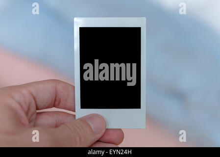 A man's hand holding an instant film print filled with a solid black space to customize with your own picture. - Stock Photo