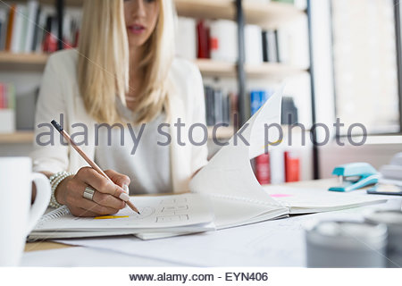 Architect drafting blueprints in office - Stock Photo