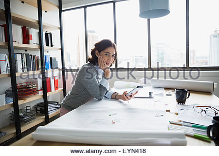 Portrait confident architect with blueprints and cell phone - Stock Photo