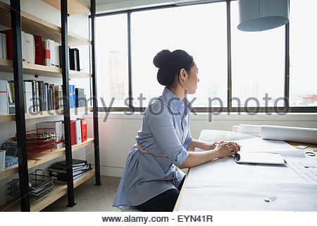Pensive architect with digital tablet blueprints looking away - Stock Photo