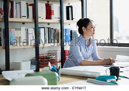 Pensive architect with blueprints looking away - Stock Photo
