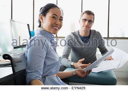 Portrait smiling architects reviewing blueprints in office - Stock Photo