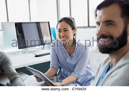 Business people with digital tablet in office - Stock Photo