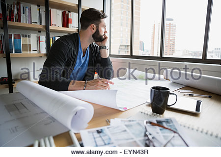 Pensive architect with blueprints looking away in office - Stock Photo
