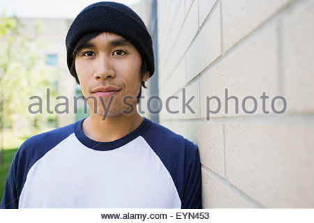 Portrait serious college student beanie leaning brick wall - Stock Photo