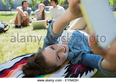 Student laying and taking selfie on campus lawn - Stock Photo