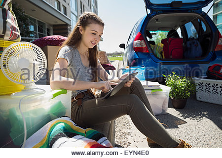 College student using digital tablet moving into dorm - Stock Photo