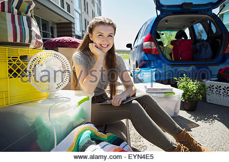 Portrait confident college student moving into college dorm - Stock Photo