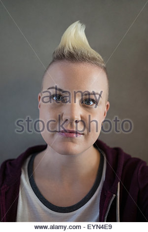 Close up portrait serious blonde woman with mohawk - Stock Photo