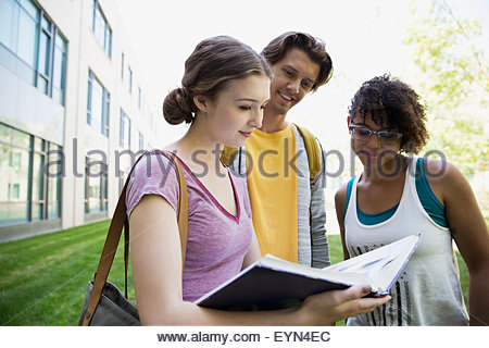 College students reading textbook on campus - Stock Photo