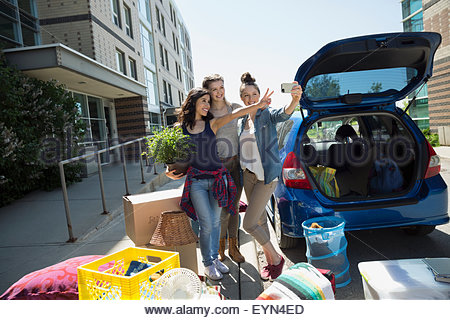 College students taking selfie moving into college dorm - Stock Photo