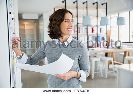 Smiling architect with blueprints at whiteboard in office - Stock Photo