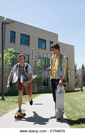 College students skateboarding on sunny campus sidewalk - Stock Photo