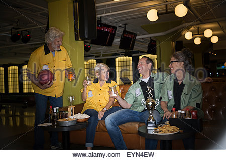 Friends in bowling shirts eating drinking bowling alley - Stock Photo