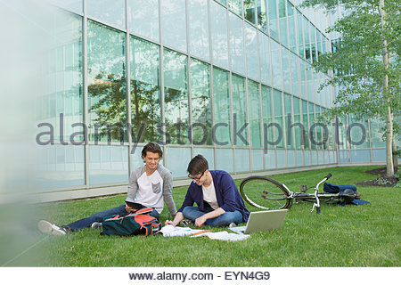 College students studying on campus lawn - Stock Photo