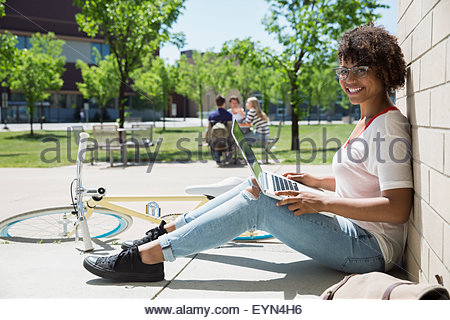 Portrait college student using laptop on sunny campus - Stock Photo