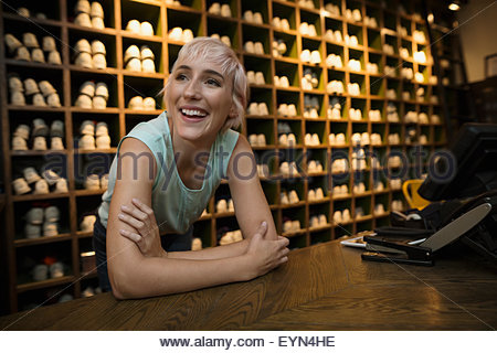 Smiling woman leaning on bowling shoes rental counter - Stock Photo