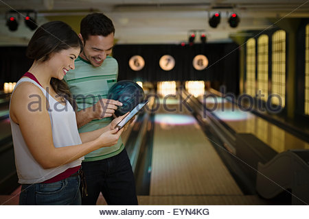 Young couple using digital tablet at bowling alley - Stock Photo