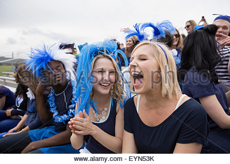 Enthusiastic woman screaming from bleachers at sports event - Stock Photo