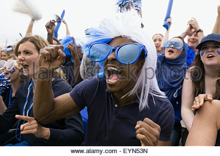 Enthusiastic fan in oversized blue sunglasses cheering - Stock Photo