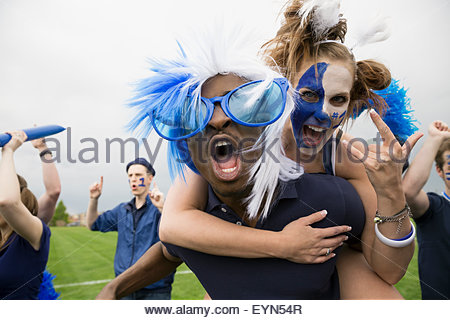 Portrait enthusiastic fans in blue piggybacking and celebrating - Stock Photo