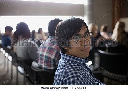 Portrait confident student sitting in auditorium audience - Stock Photo