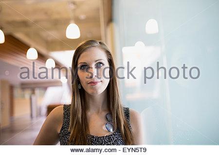 Portrait confident woman leaning on window - Stock Photo