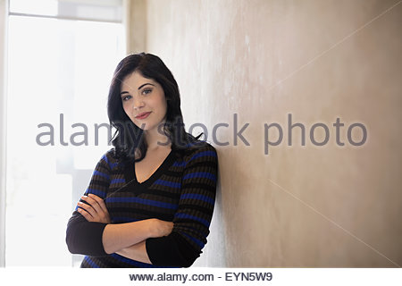 Portrait confident woman with arms crossed leaning wall - Stock Photo