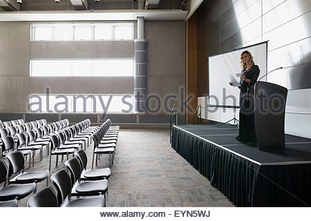 Woman reviewing notes on stage in empty auditorium - Stock Photo