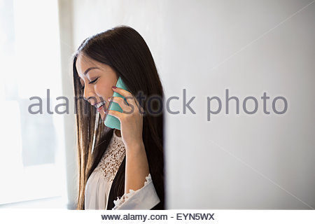 Woman talking on cell phone looking down - Stock Photo