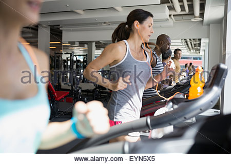 Determined woman running on treadmill at gym - Stock Photo