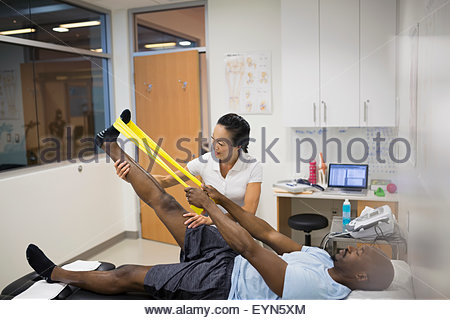 Physical therapist guiding patient using resistance band leg - Stock Photo