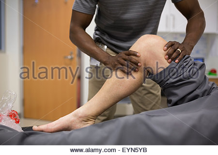 Physical therapist stretching patient knee - Stock Photo