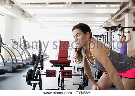 Woman resting with hands on knees at gym - Stock Photo