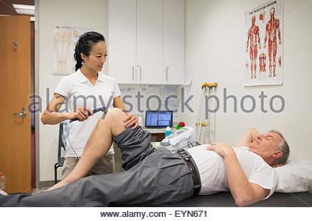 Physical therapist using ultrasound probe on patient knee - Stock Photo