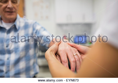 Close up physical therapist feeling patient hand - Stock Photo