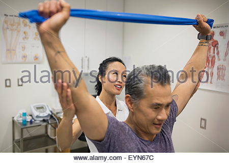Physical therapist guiding patient pulling resistance band - Stock Photo