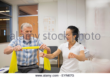 Physical therapist guiding patient with resistance band - Stock Photo