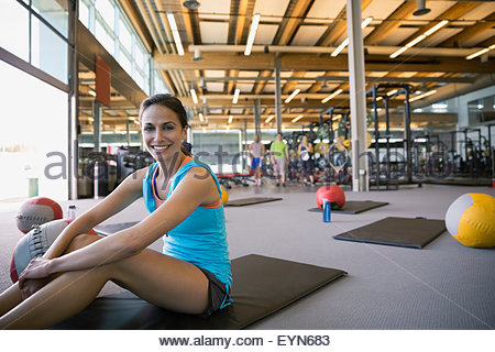 Portrait smiling woman on exercise mat in gym - Stock Photo