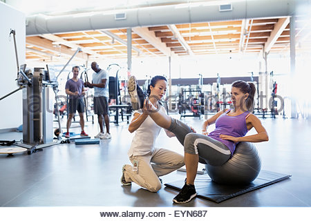 Physical therapist stretching patient leg on fitness ball - Stock Photo