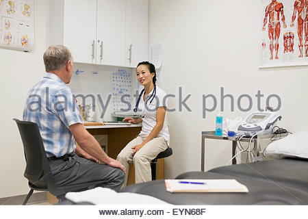 Physical therapist and patient talking in examination room - Stock Photo