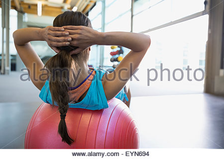 Woman doing fitness ball sit-ups at gym - Stock Photo