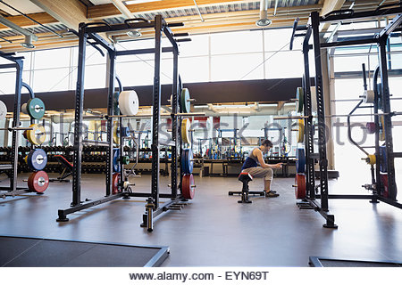 Man sitting on weightlifting bench at gym - Stock Photo