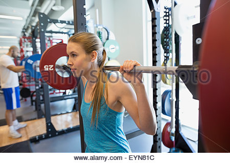 Woman doing squats with barbell in gym - Stock Photo
