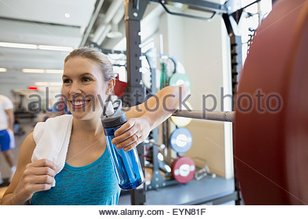 Smiling woman drinking water at barbell in gym - Stock Photo