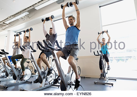 Spin class holding barbells overhead stationary bikes gym - Stock Photo
