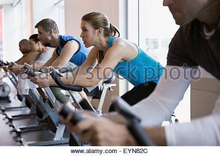 Focused woman on stationary bike in spin class - Stock Photo