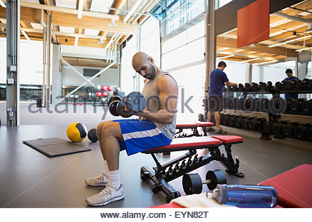Man doing dumbbell biceps curls bench at gym - Stock Photo